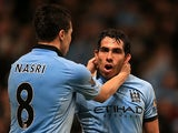 Carlos Tevez is congratulated by teammates Samir Nasri after scoring against Wigan on April 17, 2013