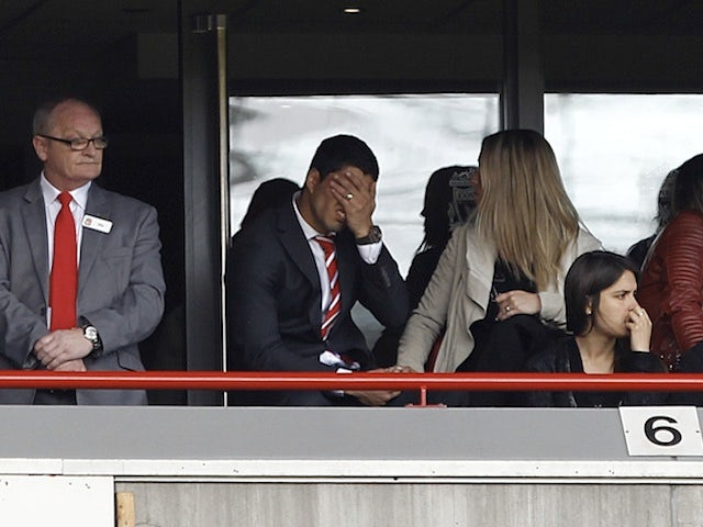 Liverpool's Luis Suarez watches the game against Everton from the stands on May 5, 2013