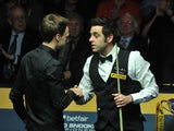 Ronnie O'Sullivan shakes hands with Judd Trump after winning the semi final match on May 4, 2013