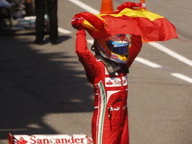 Ferrari driver Fernando Alonso of Spain celebrates his victory after wining the Formula One Spanish Grand Prix on May 12, 2013