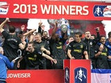 Wigan Athletic players celebrate on the pitch after beating Manchester City to win the FA Cup on May 11, 2013