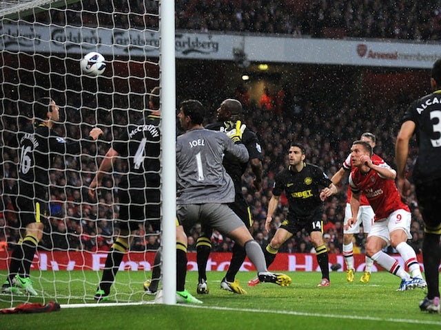 Arsenal forward Lukas Podolski scores against Wigan on May 14, 2013
