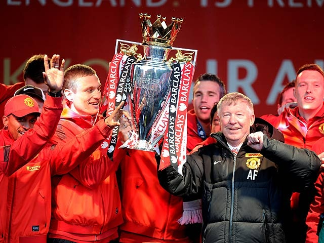 Manchester United boss Sir Alex Ferguson and his players celebrate with the Premier League trophy during the winners parade on May 13, 2013