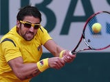 Janko Tipsarevic returns the ball to Nicolas Mahut during their first round match of the French Open on May 29, 2013