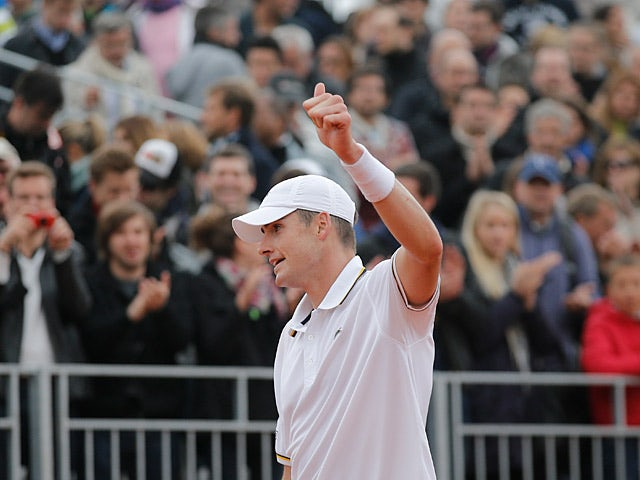 John Isner celebrates after defeating Ryan Harrison during their second round match of the French Open on May 31, 2013