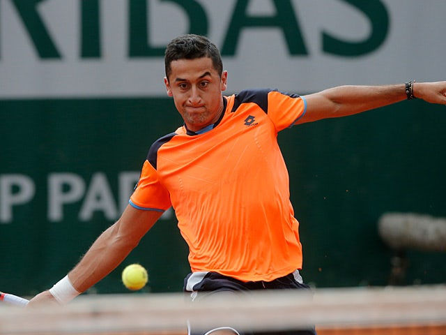 Nicolas Almagro returns the ball to Edouard Roger-Vasselin during their second round match of the French Open on May 29, 2013