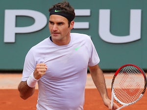 Roger Federer celebrates after defeating Julien Benneteau during their third round match of the French Open on May 31, 2013