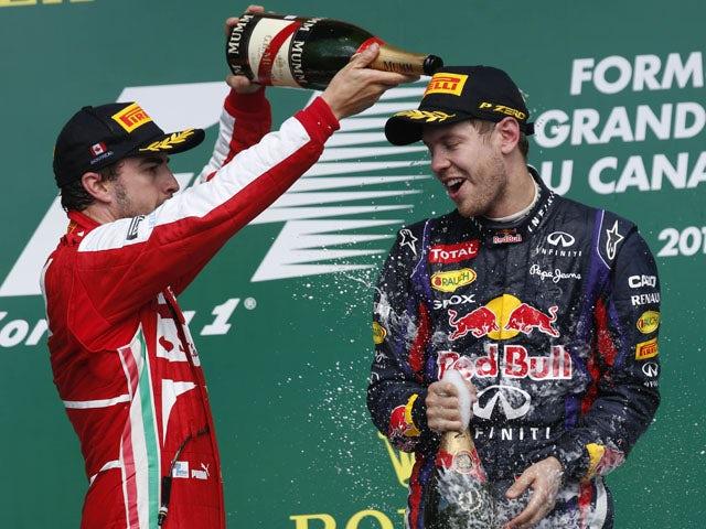 Second place Ferrari driver Fernando Alonso celebrates on the podium spraying champagne to the winner Red Bull driver Sebastian Vettel on June 9, 2013
