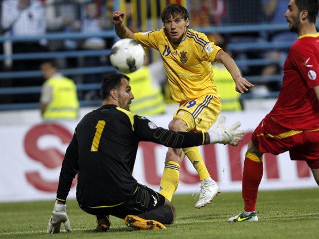 Ukraine's Denys Garmash scores past Montenegro's goalkeeper Mladen Bozovic during their World Cup qualifying match on June 7, 2013