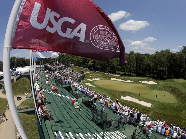 Spectators watch golfers on the 17th green during practice for the U.S. Open golf tournament at Merion Golf Club on June 12, 2013