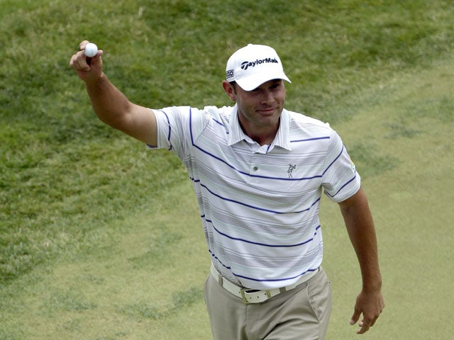 Shawn Stefani shows off the ball to the gallery after hitting a hole in one on the 17th hole during the fourth round of the U.S. Open golf tournament on June 16, 2013
