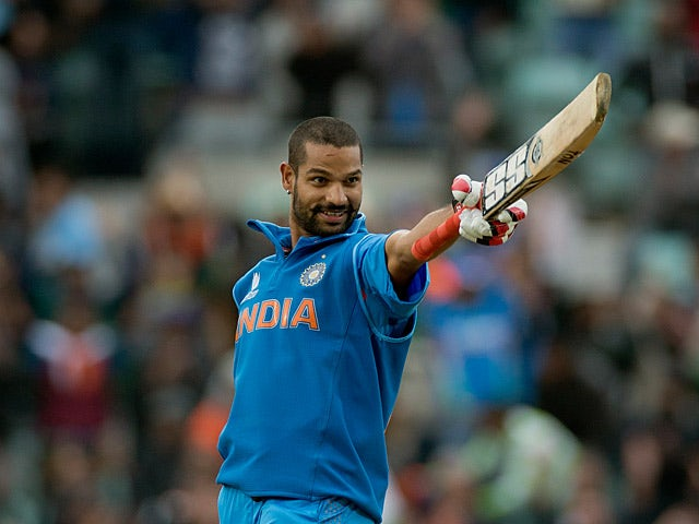 India's Shikhar Dhawan celebrates his century during the ICC Champions Trophy against the West Indies on June 11, 2013