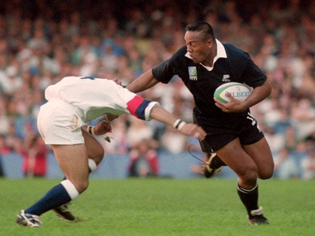 Jonah Lomu holds of a challenge from an England player.
