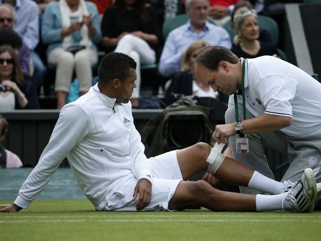 France's Jo-Wilfried Tsonga receives treatment in his match against Latvia's Ernests Gulbis during their second round match at Wimbledon on June 26, 2013