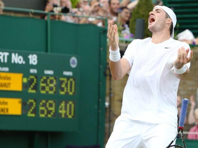 John Isner celebrates beating Nicolas Mahut at Wimbledon.