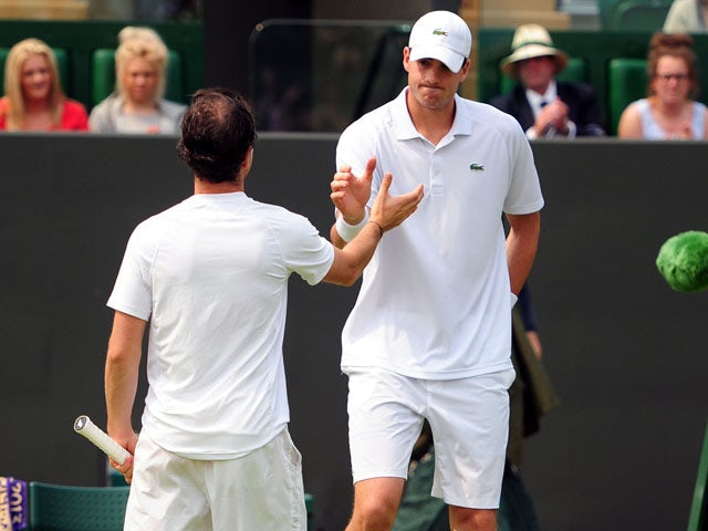 USA's John Isner shakes hands with France's Adrian Mannarino after retiring from the match during day Three of the Wimbledon Championships on June 26, 2013