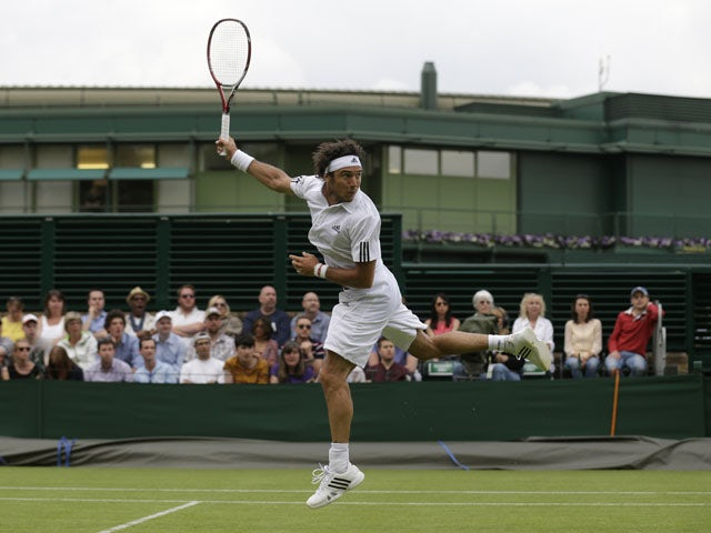 Juan Monaco of Argentina looks over his shoulder to track the trajectory of a lob by Rajeev Ram of the United States during their Men's second round singles match on June 26, 2013