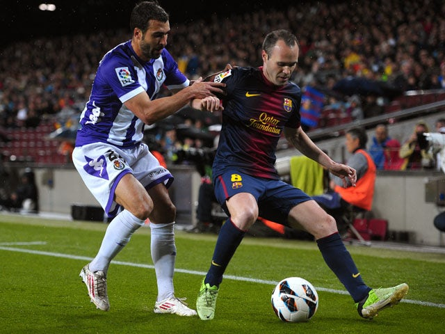 Valladolid's Mikel Balenziaga tries to tackle Barcelona's Andres Iniesta during the La Liga clash on May 19, 2013