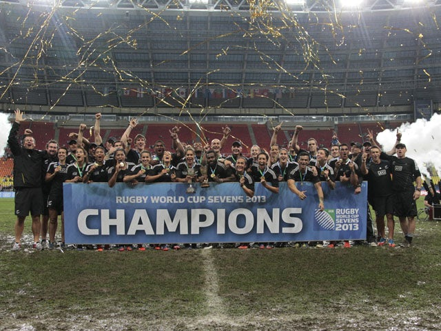 New Zealand's All Blacks celebrate with their men and women trophies after winning both at the Rugby Sevens World Cup on June 30, 2013