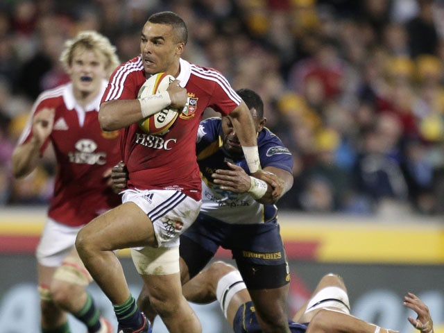 British and Irish Lions player Simon Zebo breaks through the tackle of ACT Brumbies' players Jordan Smiler during the tour match on June 18, 2013