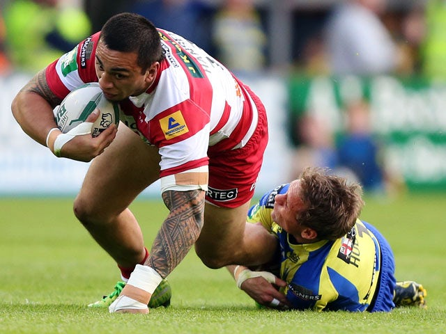 Warrington Wolves Brett Hodgson tackles Wigan Warriors Harrison Hansen during the Super League match on June 24, 2013
