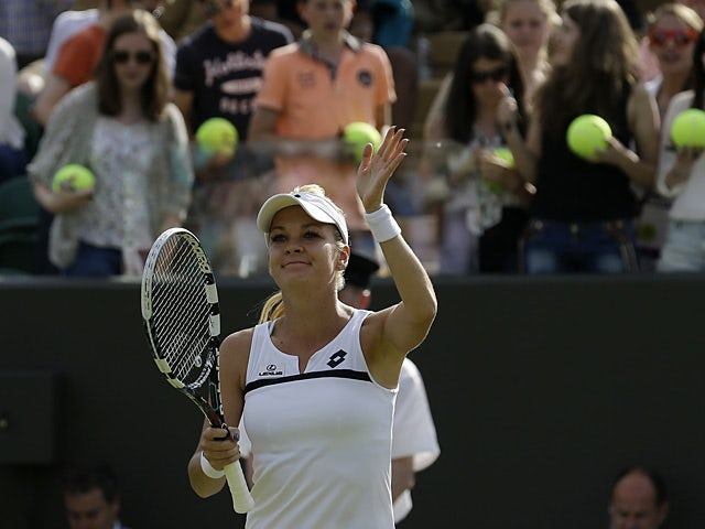 Agnieszka Radwanska waves to the crowd as she celebrates her win over Tsvetana Pironkova during their Wimbledon match on July 1, 2013
