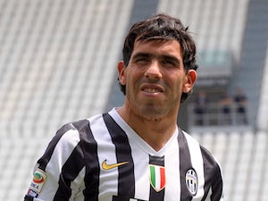 Juventus signing Carlos Tevez wears his new clubs shirt before a press conference on June 26, 2013