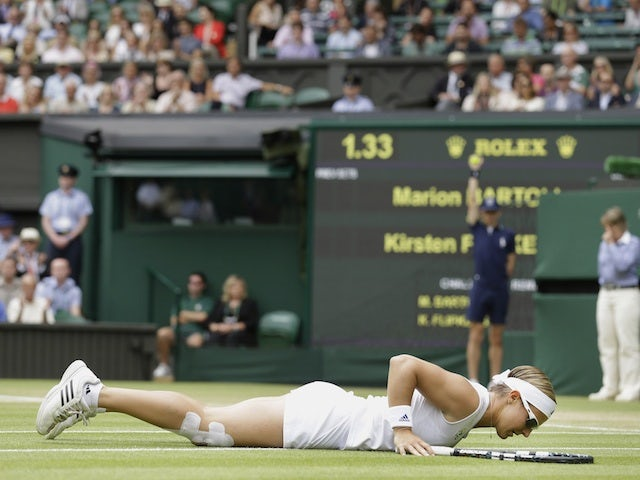 Kirsten Flipkens lays on the ground after losing a point to Marion Bartoli on July 4, 2013