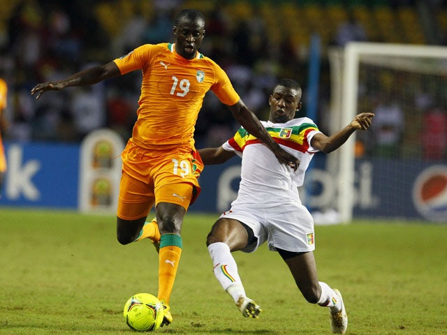 Mali's Samba Sow dives in to tackle Ivory Coast's Yaya Toure during the African Cup of Nations match on February 8, 2012