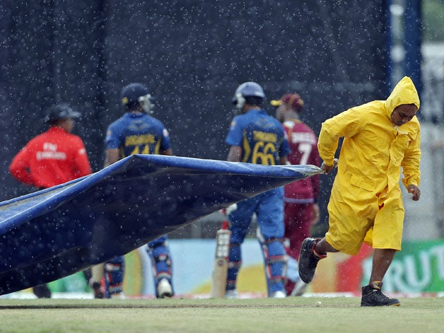 A grounds keeper pulls the tarpaulin to cover the pitch during the match between Sri Lanka and West Indies on July 7, 2013
