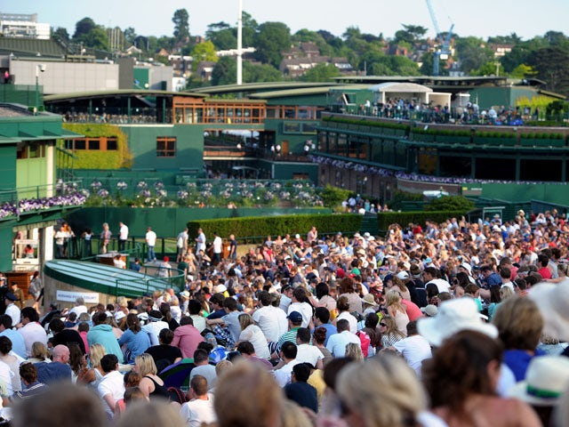 Fans on Murray Mount watch the match between Great Britain's Andy Murray and Poland's Jerzy Janowicz on the big screen on July 5, 2013
