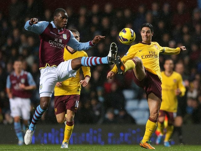 Christian Benteke challenges Mikel Arteta for possession.