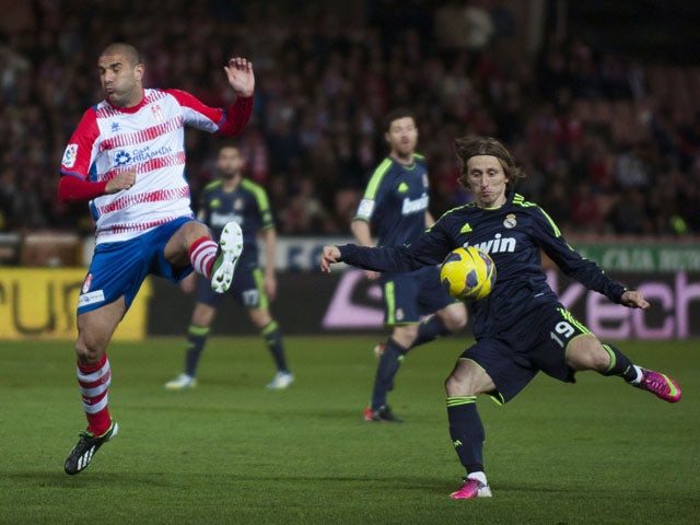 Granada's Carlos Aranda jumps to block a shot from Real Madrid's Luka Modric during the La Liga match on February 2, 2013