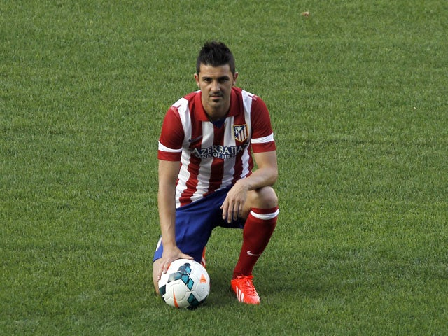 Atletico de Madrid's new player David Villa poses for a picture during his presentation at the Vicente Calderon Stadium on July 15, 2013