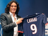 New Paris Saint Germain signing Edinson Cavani poses with his new team's shirt during a press conference on July 16, 2013