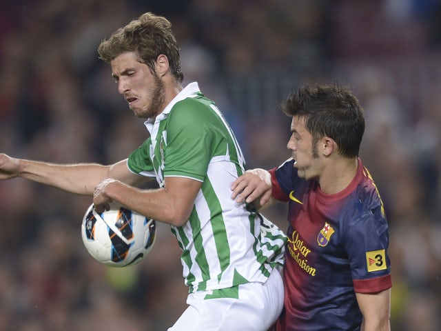 Betis's Ruben Perez duels for the ball with Barcelona's David Villa during the La Liga match on May 5, 2013