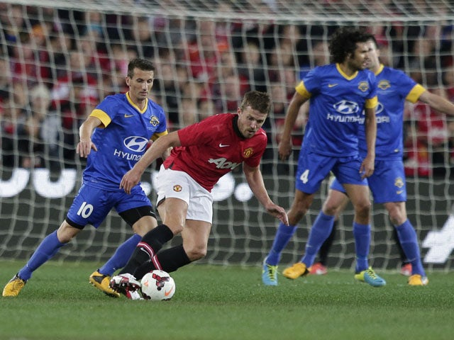 Manchester United Michael Carrick steals the ball off Sydney Allstars' Liam Miller during the exhibition match on July 20, 2013