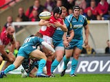 London Welsh's Tom Bristow fumbles the ball before being tackled by Gloucester's Dave Lewis on September 30, 2012