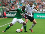 Werder Bremen's Cedrick Makiadi and Fulham's Dimitar Berbatov battle for the ball during a friendly match on July 28, 2013