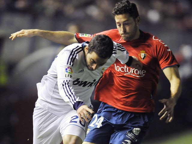 Osasuna's Damia Abella duels with Real Madrid's Gonzalo Higuain during the La Liga match on January 12, 2013