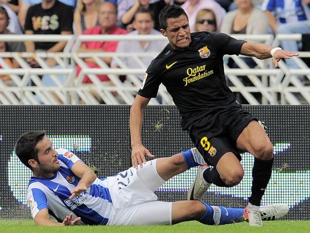 Real Sociedad's Daniel Estrada challenges Barcelona's Alexis Alejandro during the La Liga match on September 10, 2011