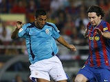 Almeria's Hernan Bernardello vies for the ball with Barcelona's Lionel Messi on October 3, 2009
