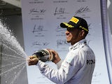 Lewis Hamilton celebrates on the podium with champagne after winning the Hungarian grand prix on July 28, 2013