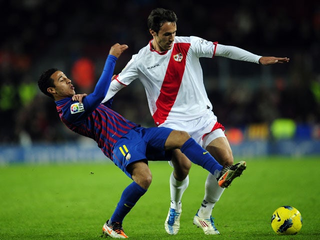 Rayo Vallecano's Rafa Garcia duels for the ball with  FC Barcelona's Thiago Alcantara during the La Liga match on November 29, 2011