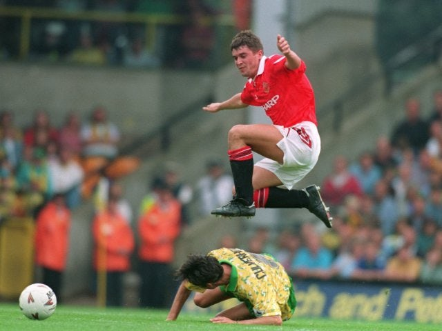 Roy Keane leaps over a Norwich City midfielder at Carrow Road.