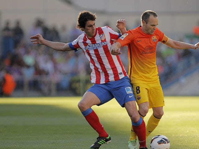 Atletico Madrid's Tiago Mendes attempts to tackle FC Barcelona's Andres Iniesta during the La Liga match on May 12, 2013