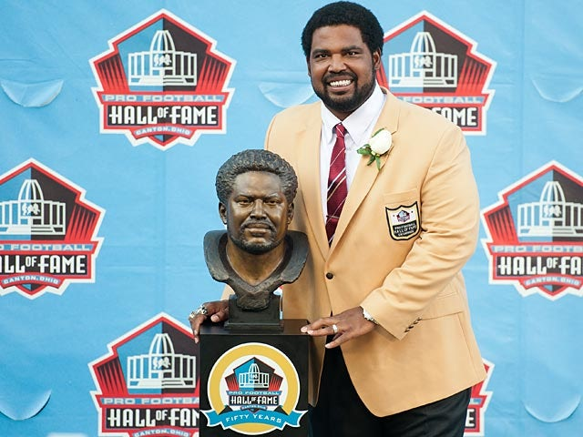 Former Baltimore Ravens' Jonathan Ogden poses with his Hall of Fame bust at the NFL Class of 2013 Enshrinement Ceremony on August 3, 2013
