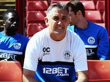 Wigan manager Owen Coyle smiles in the dugout before kick off against Barnsley on August 3, 2013