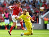 Forest's Simon Cox shoots past Huddersfield's Joel Lynch on August 3, 2013
