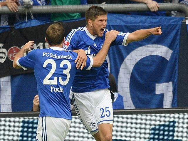 Schalke's Klaas-Jan Huntelaar is congratulated by team mate Christian Fuchs after scoring his second goal against Hamburg on August 11, 2013